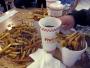 Nötter och pommes frites i salig röra på bord, i muggar och utspridda över golvet